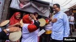 Anies Baswedan (kanan) berbicara dengan pendukungnya pada saat kampanye pemilihan kepala daerah DKI Jakarta. (Antara Foto/Muhammad Adimaja/via REUTERS)