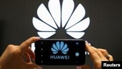 资料照:一支手机屏幕上显示的华为标识。