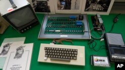 An Apple 1 Computer from 1976 made by Steve Jobs and Steve Wozniak is presented at an auction house in Cologne, Germany, Saturday, Nov. 16, 2013. (AP Photo/Martin Meissner)