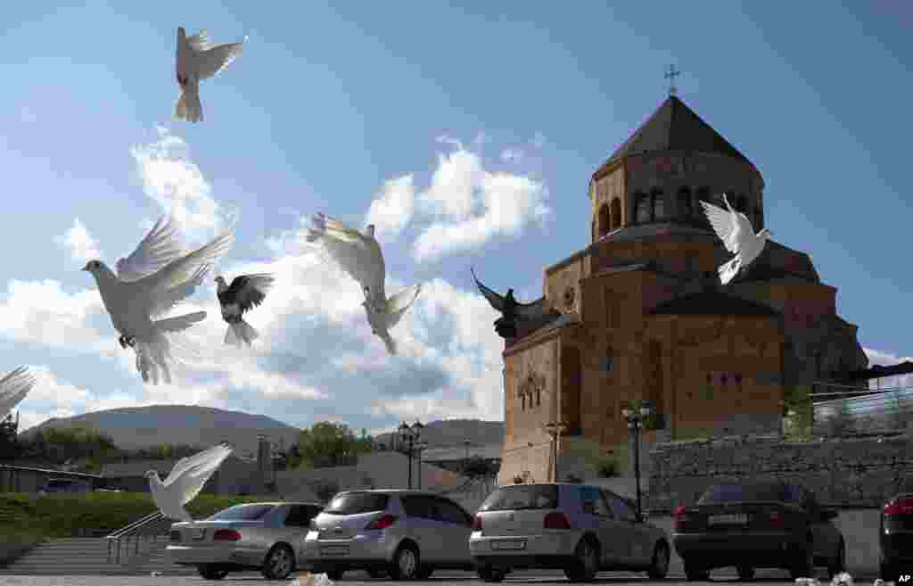 Pigeons fly near Holy Mother of God Cathedral in Stepanakert during a military conflict in the separatist region of Nagorno-Karabakh, Friday, Oct. 9, 2020. The latest outburst of fighting between Azerbaijani and Armenian forces began Sept. 27 and marked t