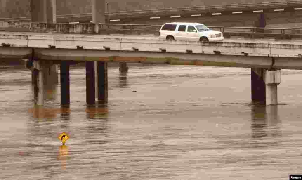 A SUV drives over flooded White Oak Bayou in Houston, Texas, USA, Oct. 25, 2015. Precipitation was expected to intensify over the weekend as moisture from tropical depression Patricia, which struck the Pacific coast of Mexico as a very powerful hurricane, meets with a storm system coming from the west and over Texas.