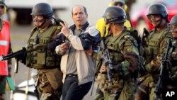 El guerrillero colombiano de las FARC alias Simón Trinidad es escoltado por soldados colombianos en una base militar en Bogotá, luego de su captura el 3 de enero de 2004. Trinidad cumple condena en Estados Unidos.