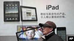 បុរសម្នាក់ឈរនៅក្បែរស្លាកសញ្ញាផ្សាយពាណិជ្ជកម្ម អាយផាដ (iPad) របស់ក្រុមហ៊ុន អាប់ផល (Apple) នៅទីក្រុងស៊ៀងហៃ ប្រទេសចិននៅខែមករា ឆ្នាំ២០១១។
