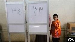 Seorang wanita didampingi anaknya memberikan suaranya di TPS Giza, Mesir (21/12).