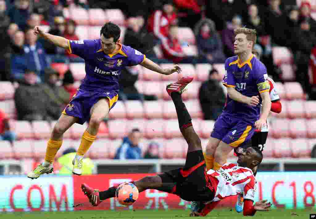 Sunderland's El-Hadji Ba, bottom, vies for the ball with Kidderminster Harriers' Jack Dyer, left, and captain Kyle Storer, right, during their English FA Cup fourth round soccer match at the Stadium of Light, Sunderland, England.