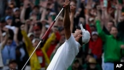 Adam Scott, of Australia, celebrates after making a birdie putt on the second playoff hole to win the Masters golf tournament, Apr. 14, 2013, in Augusta, Ga.
