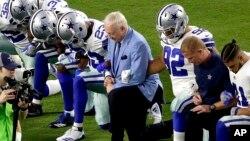 Para pemain klub NFL Dallas Cowboys, dan pemilik klub Jerry Jones, berlutut sebelum pertandingan melawan klub Arizona Cardinals, di Glendale, Arizona, Senin malam (25/9).
