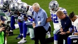 FILE - The Dallas Cowboys, led by owner Jerry Jones, center, take a knee prior to a NFL football game against the Arizona Cardinals, in Glendale, Arizona, Sept. 25, 2017.
