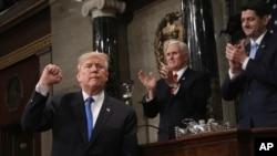 도널드 트럼프 미국 대통령(왼쪽)이 지난해 1월 의회에서 첫 국정연설을 마친 후 주먹을 들어보이고 있다. 마이크 펜스 미국 부통령(가운데)과 폴 라이언 하원의장이 박수를 보내고 있다.