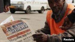 짐바브웨 수도 하라레 주민이 무가베 대통령 자택연금 소식이 머릿기사로 실린 신문을 읽고 있다.