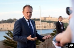 FILE - European Council President Donald Tusk speaks with the media prior to an EU summit outside his hotel in Valletta, Malta, Feb. 2, 2017.