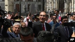Peru's President Martin Vizcarra holds up a folder as he waves next to next to Prime Minister Cesar Villanueva, left, as they leave the government palace for Congress where he plans to urge legislators to declare an emergency at the attorney general's office, Jan. 2, 2018.