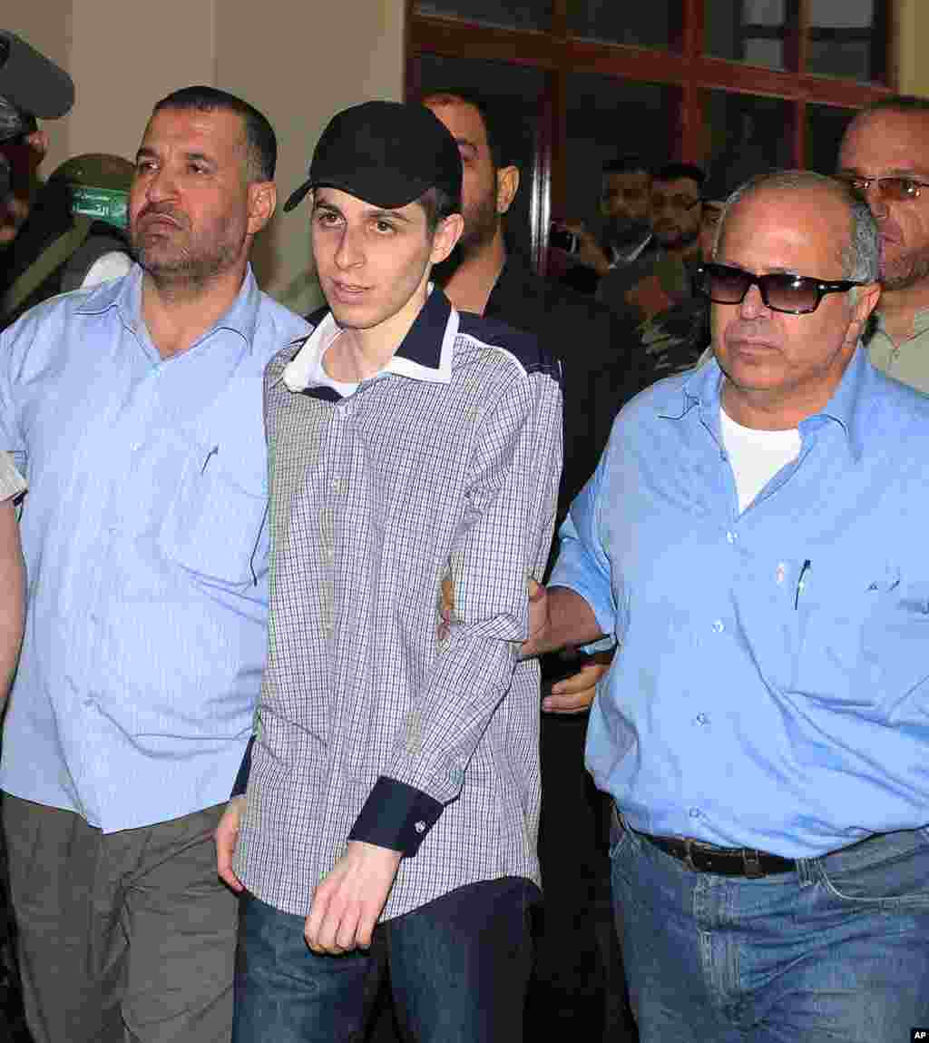 Israeli soldier Gilad Shalit (C) is escorted by intelligence officers upon his arrival at the Egyptian side of the Rafah border crossing on October 18, 2011 following his release after 5 years of Hamas captivity under the terms of an Egyptian-mediated dea