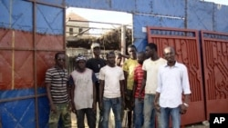 Elhadji Moctar Gueye (far right) with his team of employees outside his metallic workshop in Dakar, December 19, 2011.
