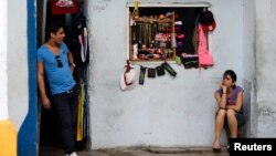 Vendors await customers at their private imported clothing outlet, Havana, Oct. 5, 2013.