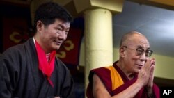 Lobsang Sangay, left, the new prime minister of Tibet's government in exile, stands next to Tibetan spiritual leader the Dalai Lama as he greets the crowd at his swearing-in ceremony at the Tsuglakhang Temple in Dharmsala, India, Monday, Aug. 8, 2011.