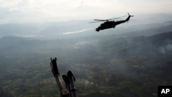 FILE - a military helicopter flies over the VRAEM region, in Pichari, Peru, Sept. 19, 2014. The region in the Apurimac, Ene and Mantaro River Valleys, or VRAEM, is the world's No. 1 coca-growing region.