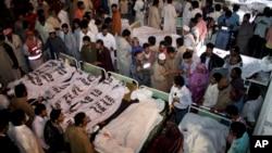 Thân nhân đứng quanh thi hài các nạn nhân bị giết trong vụ tấn công tự sát, Lahore, Pakistan 2/11/14