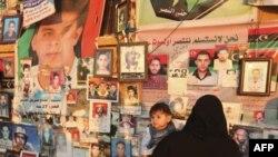 Bir anne askerler tarafından öldürülen kişilerin resimleri arasında yakınlarını arıyor