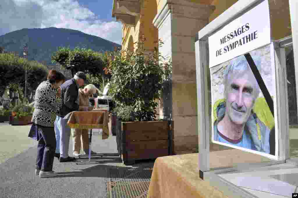 Residents of St. Martin Vesubie, southern France, sign a tribute album to pay respect to French mountaineer, Herve Gourdel, after he was beheaded by militants in Algeria the day before, Sept. 25, 2014.