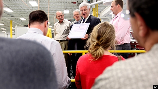 Republican presidential hopeful, former House Speaker Newt Gingrich, center, prepares to sign the Strong America Now pledge, while touring C&M Machine Products in Hudson, New Hampshire, June 8, 2011.