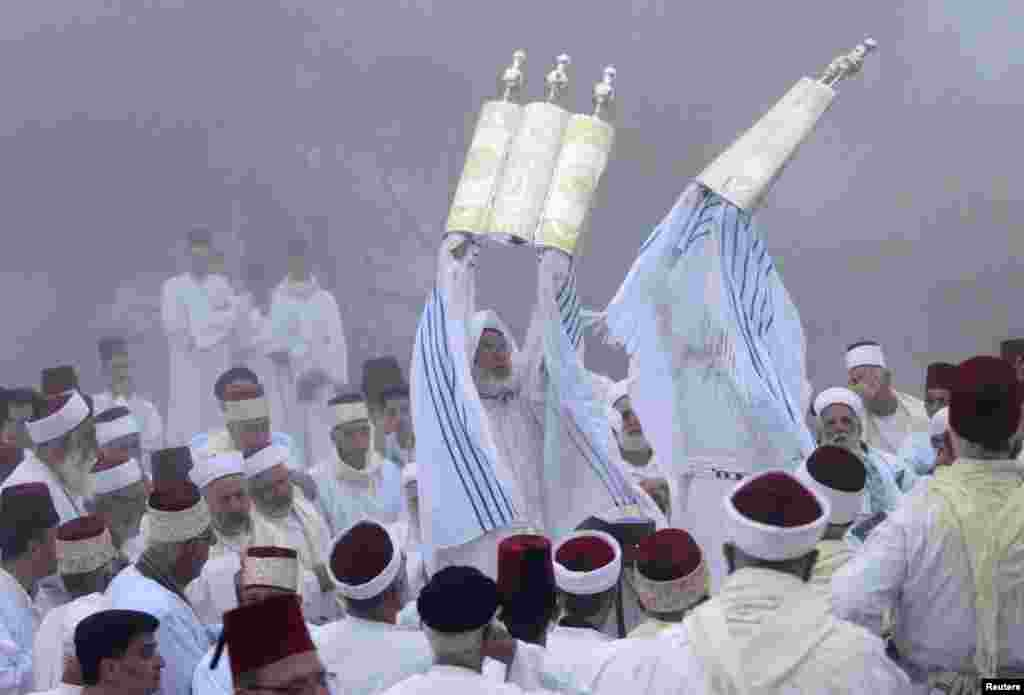 Members of the Samaritan hold up Torah scrolls during a traditional pilgrimage marking the holiday of Shavuot, atop Mount Gerizim near the West Bank city of Nablus. The Samaritans, who trace their roots to the biblical Kingdom of Israel in what is now the northern occupied West Bank, observe religious practices similar to those of Judaism.