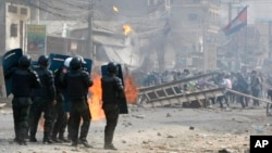 FILE: Cambodian riot police prepare to confront with garment workers throwing stones and bricks near a factory on the Stung Meanchey complex on the outskirts of Phnom Penh, Cambodia, Friday, Jan. 3, 2014.