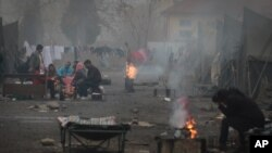 Syrian refugees try to stay warm near open fires in front of their unheated tents in a refugee camp in the town of Harmanli, Bulgaria, Thursday, Nov. 21, 2013. AP Photo/Valentina Petrova