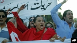 People chant slogans during a demonstration held after a group of individuals attacked the CinemAfricArt building to protest a controversial film called 'No God, No Master,' in Tunis, July 7, 2011