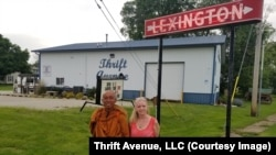 Karen Wingo (L), A Manager of Thrift Avenue store and Buddhist monk Sutham Nateetong (R) pose at the Lexington sign along the U.S Historic Route 66 in Lexington, IL. May 29, 2019.