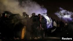 明尼苏达州布鲁克林中心警察局外的抗议者在来自化学刺激物的烟雾中用雨伞防护自己。(2021年4月13日)