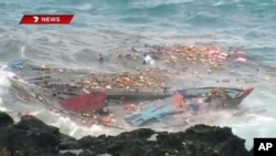 An TV grab shows people floating amid and hanging onto the splintered remains of the wooden boat carrying refugees traveling from Asia after it smashed into the rocky coastline of Christmas Island in rough sea, (File)