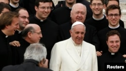 Pope Francis poses with a group of priests at the end his Wednesday general audience in Saint Peter's square at the Vatican Feb. 26, 2014.