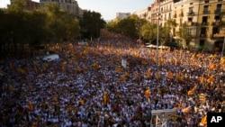 """Warga melakukan pawai kemerdekaan sambil melambai-lambaikan bendera """"estelada""""yang melambangkan kemerdekaan Catalonia dalam aksi di kota Barcelona, Spanyol hari Minggu (11/9)."""