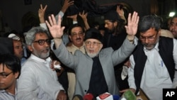 Pakistani cleric Tahir-ul-Qadri waves to his supporters after reaching Lahore, Pakistan, Monday, June 23, 2014.