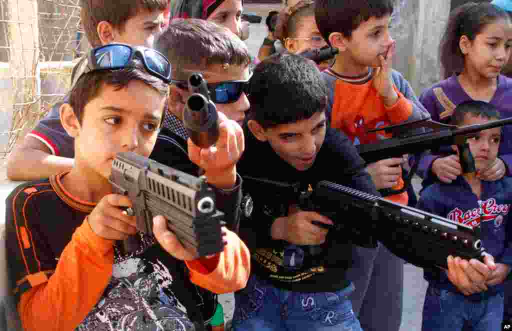 Syrian children play with toy weapons at a refugee camp in the southern port city of Sidon, Lebanon, Oct. 27, 2012 during the Eid Al-Adha holiday.