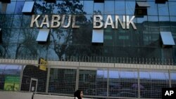 An Afghan girl walks past by Kabul Bank main office in Kabul, Afghanistan. (File Photo)