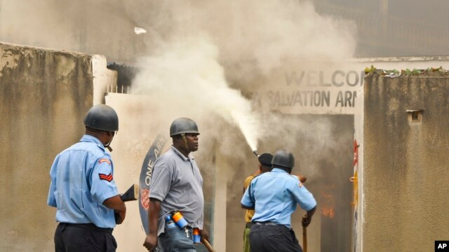 Policeman armed with pistol and tear gas patrols while firemen extinguish fire set by rioting youth at Salvation Army Church, Mombasa, Kenya, Oct. 4, 2013.