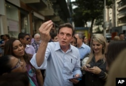 FILE - In this Sept. 29, 2014 file photo, retired Pentecostal Bishop Marcelo Crivella campaigns for the governorship of Rio de Janeiro state in Brazil's Copacabana. Amid reports that a play with a transgender Jesus might go to Rio de Janeiro's Museum