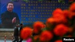 បុរសៗដើរកាត់ផ្ទាំងរូបរបស់លោកប្រធានាធិបតី Xi Jinping នៅថ្ងៃទី២ នៃការប្រជុំពេញអង្គនៃគណៈកម្មាធិការកណ្តាលនៃគណបក្សកុម្មុយនិស្តចិនទី១៨ ក្នុងក្រុងប៉េកាំង កាលពីថ្ងៃទី២៥ ខែតុលា ឆ្នាំ២០១៦។