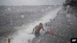 Ombak mengenai seorang warga Filipina ketika mengambil sandal karetnya di Manila Bay, Filipina, 10 Mei 2015.