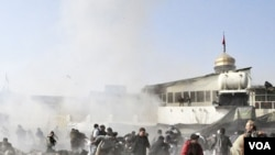 Warga Syiah yang tengah merayakan hari raya Ashura berlarian setelah ledakan bom dekat masjid di Kabul, Selasa (6/12).