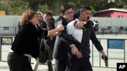 Bà Dilek Dundar, vợ nhà báo Can Dundar, và luật sư (thứ hai bên trái), chế ngự một tay súng ngay sau khi người này tấn công ông Dundar bên ngoài tòa án thành phố ở Istanbul, ngày 06 tháng 5 năm 2016.