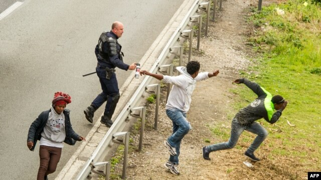 Police officer sprays tear gas at migrants trying to access Channel Tunnel on the A16 highway in Calais, northern France, June 23, 2015.
