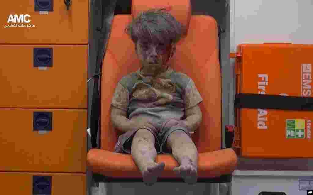 រូបថតចេញពីវីដេអូផ្តល់ឲ្យដោយក្រុមសកម្មជនប្រឆាំងរដ្ឋាភិបាលស៊ីរី Aleppo Media Center (AMC) បង្ហាញពីកុមារាម្នាក់អង្គុយនៅក្នុងរថយន្តសាមុយ បន្ទាប់ពីត្រូវបានយកចេញពីអគារមួយដែលរងការវាយប្រហារតាមអាកាស នៅក្រុង Aleppo កាលពីថ្ងៃទី១៧ ខែសីហា ឆ្នាំ២០១៦។