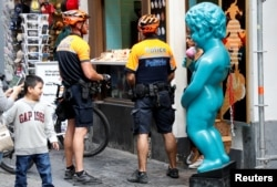 FILE - Belgian police officers are seen next to a replica of Brussels' iconic Manneken Pis statue during a patrol in central Brussels, Belgium, May 31, 2017.