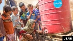 Fatima, 10, washes her face at a water tank provided by UNICEF in Tinah Camp on September 5, 2016. USAID has been supporting UNICEF to provide safe drinking water at the displacement camp in Ninewa Governorate to keep families, especially kids, healthy.