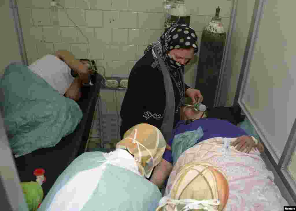 People wounded in what the Syrian government said was a chemical weapons attack breathe through oxygen masks as they are treated at a hospital in Aleppo, March 19, 2013.