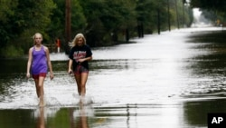 Two women walk along the flooded Parish Barn Road in Iowa, La., Aug. 30, 2017.