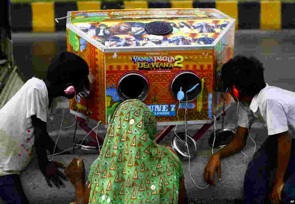 "An Indian woman and two boys watch a trailer of the upcoming Bollywood film ""Yamla Pagla Deewana 2"" on a traditional biscope in Mumbai, India."